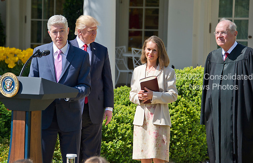 Associate Justice of the United States Supreme Court Neil Gorsuch, left, makes remarks after taking the Oath of Office from Associate Justice Anthony Kennedy, right, in the Rose Garden of the White House in Washington, DC on Monday, April 10, 2017.  US President Donald J. Trump, center left, and Louise Gorsuch, right center, look on.<br /> Credit: Ron Sachs / CNP<br /> (RESTRICTION: NO New York or New Jersey Newspapers or newspapers within a 75 mile radius of New York City)