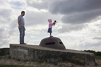 A visitor looks on as his daughter holds a doll while standing on top of a French bunker at Fort Douaumont in Verdun, Meuse, France, August 22, 2014. 2014 marks 100th anniversary of the World War I.