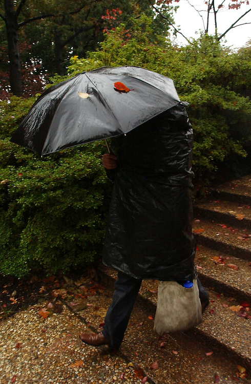A man uses an umbrella and a garbage bag to shield himself from Monday's ran, while walking through a park near Russell Building.