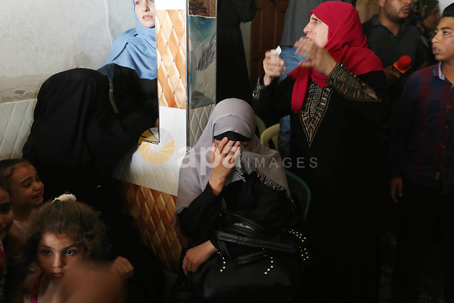 Relatives of Palestinian Ahmed Qutoosh, 23, who died of his wounds endured during clashes with Israeli troops in a tent city protest where Palestinians demand the right to return to their homeland at the Israel-Gaza border, mourn during his funeral in Nuseirat, in the central Gaza Strip, on May 25, 2018. Photo by Ashraf Amra