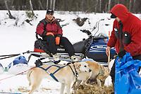Volunteer checkpoint helper, Adam Nikolai, takes a break on his snowmachine as Ramey Smyth straws his dogs at the Nikolai checkpoint during Iditarod 2008