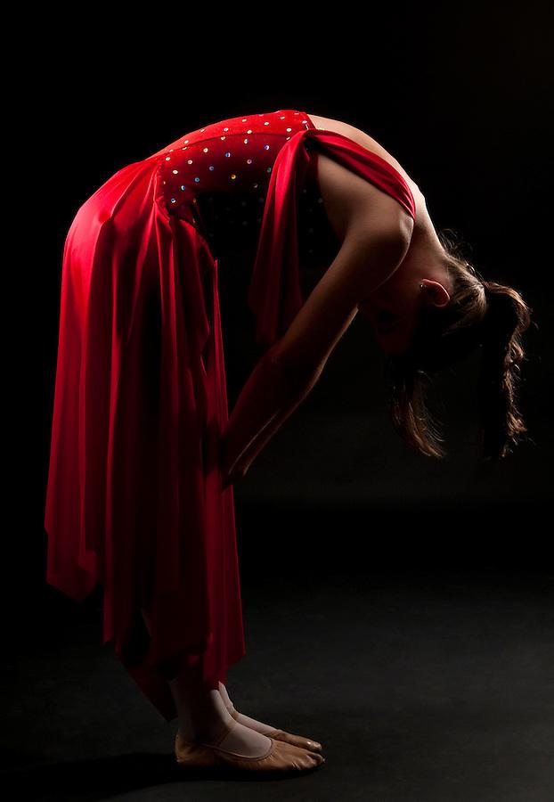 Young caucasian ballerina posing in dim light. Resting and pensive.