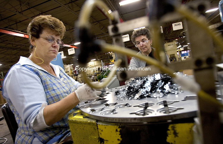 WATERBURY, CT. 14 November 2008-111408SV03--From left, Maria Santos and Halina Kania, machine operators for ITW/CPI put parts together to be used for access panels in automobiles in Waterbury Friday.<br /> Steven Valenti Republican-American