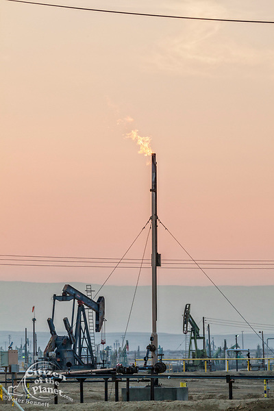 Flares burning off gas at Belridge Oil Field and hydraulic fracking site which is the fourth largest oil field in California. Kern County, San Joaquin Valley, California, USA