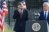 United States President Barack Obama wipes his face due to the heat and humidity after his remarks at the 12th anniversary commemoration of the 9/11 terrorist attacks at the Pentagon Memorial at the Pentagon in Washington, DC on September 11, 2013. Nearly 3,000 people were killed in the attacks in New York, Washington and Shanksville, Pennsylvania.   At right is Secretary of Defense Chuck Hagel. <br /> Credit: Pat Benic / Pool via CNP