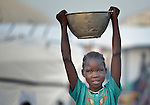 A displaced girl carries a bowl of grain inside a United Nations base in Malakal, South Sudan. More than 20,000 civilians have lived inside the base since shortly after the country's civil war broke out in December, 2013, but renewed fighting in 2015 drove another 5,000 people into the safety of the camp.