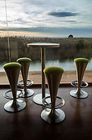 """Spain. Valencia Province. Valencia. Nou Racó restaurant.  Footstool and table. Colorful sunset over the Albufera, or L'Albufera de València ([albuˈfeɾa], meaning """"lagoon"""" in Valencian), is a freshwater lagoon and estuary on the Gulf of Valencia coast. It is the main portion of the Valencian Albufera Natural Park, with a surface area of 21,120 hectares (52,200 acres). The natural biodiversity of the nature reserve allows a great variety of flora and fauna to thrive. Though once a saltwater lagoon, dilution due to irrigation and canals draining into the estuary and the sand bars increasing in size had converted it to freshwater by the seventeenth century. Valencia (officially València) is the capital of the autonomous community of Valencia and the third-largest city in Spain. 15.12.18  © 2018 Didier Ruef"""