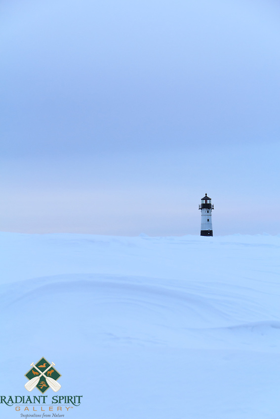 Wind-sculpted snow accentuates the shoreline near the Canal Park Lighthouse.