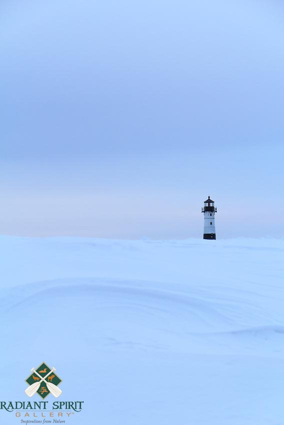 Wind-sculpted snow accentuates the shoreline near the Canal Park Lighthouse.