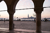 ITALY, Venice.  A view of the column's of Doge's Palace at Piazza San Marco. The island of San Giorgio Maggiore can be seen in the distance, dominated by the tower and dome of the Church of San Giorgio Maggiore.