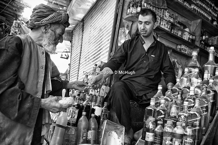 A trader sells spices, and oil in recycled whiskey bottles, at Kabul's ancient bird market, 23 August 2012. (John D McHugh