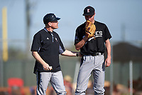 Edgewood Eagles head coach Al Brisack talks with pitcher Adam Eck (26) during the first game of a doubleheader against the Plymouth State Panthers on April 17, 2016 at Lee County Player Development Complex in Fort Myers, Florida.  Plymouth State defeated Edgewood 6-5.  (Mike Janes/Four Seam Images)