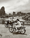 CHINA, Guilin, people traveling on motorbikes over a bridge in rural Guilin (B&W)
