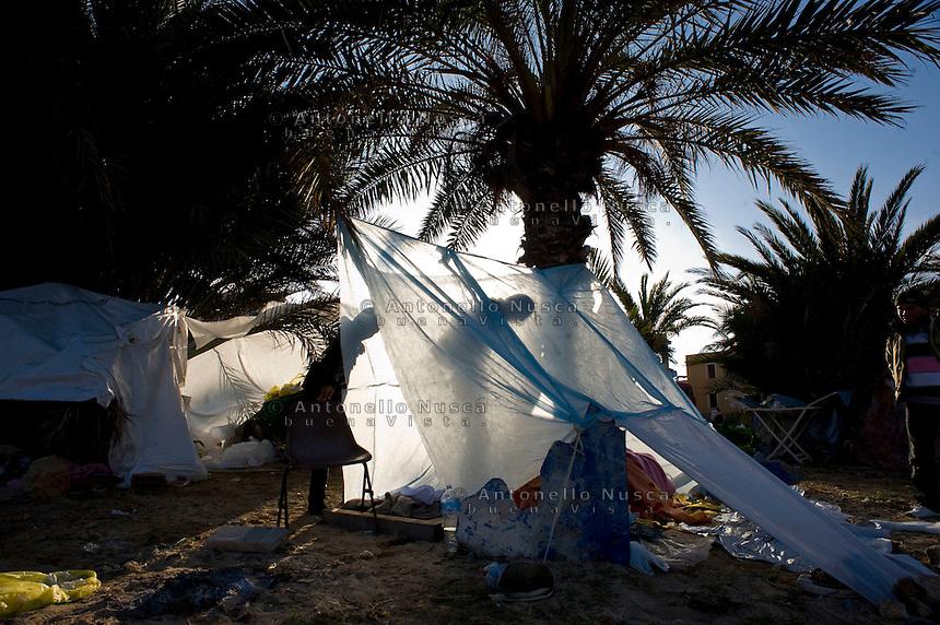 Alcuni immigrati Tunisini costruiscono una tenda dove poter passare la notte