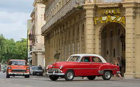 Havana, Cuba - Taxis pass in front of Hotel Plaza near Parque Central. Classic American cars from the 1950s, imported before the U.S. embargo, are commonly used as taxis in Havana.