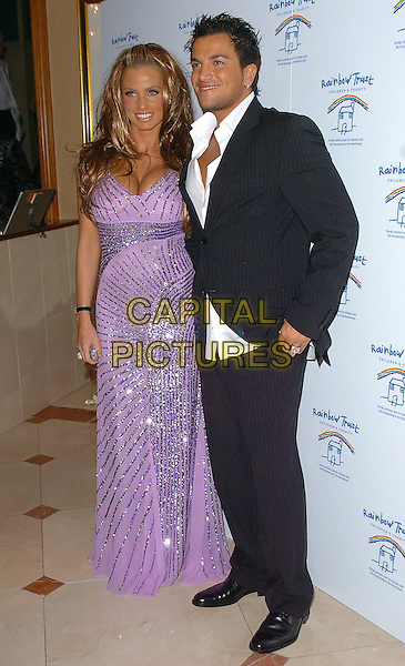 KATIE PRICE & PETER ANDRE.Rainbow Glass Slipper Ball 2005 held at the London Hilton, London..12th November 2005.UK, United Kingdom..Ref: CAN.full length with together purple floor length sparkly sequinned plunging neckline clevage dress smiling posed.www.capitalpictures.com.sales@capitalpictures.com.©Capital Pictures