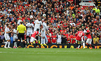 Pictured: Swansea players jump trying to block a free kick taken by Wayne Rooney of Manchester United (10). Saturday 16 August 2014<br />
