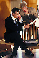 Man and woman discussing business; on cell phone; looking over documents. Normal view. Professionals. Lawyers. Businesswoman. Businessman. Denver Colorado USA.