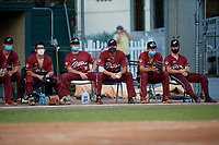 Members of the Macon Bacon sit outside the dugout to practice social distancing, while wearing protective masks, during a Collegiate Summer League game against the Savannah Bananas on July 15, 2020 at Grayson Stadium in Savannah, Georgia.  (Mike Janes/Four Seam Images)