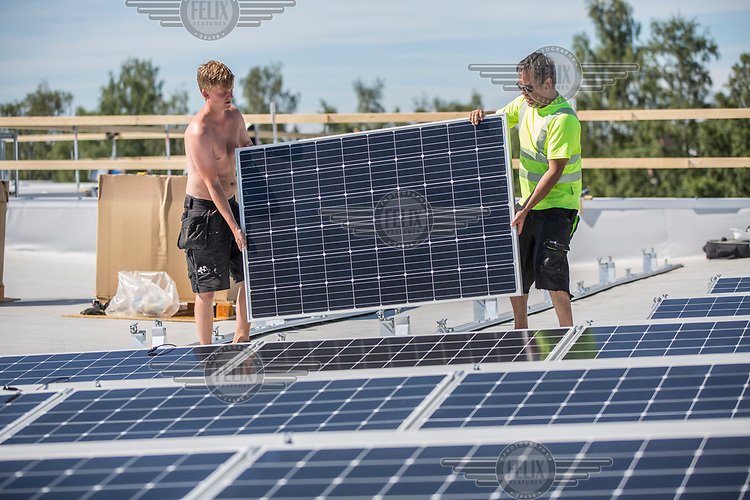 Workers install solar panels on the roof of a large food warehouse for a distributing company in Oslo. Taking advantage of the large space on the roof the company hope to go green and save a substatial amount of electric energy.