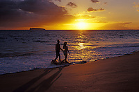 A couple walks at the water's edge enjoying a Maui sunset at Big Beach, Makena, Maui.