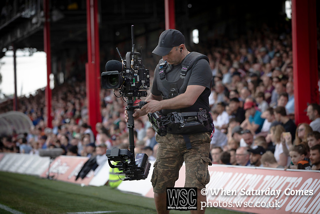 A television cameraman working in front of the new Road stand as Brentford hosted Leeds United in an EFL Championship match at Griffin Park. Formed in 1889, Brentford have played their home games at Griffin Park since 1904, but are moving to a new purpose-built stadium nearby. The home team won this match by 2-0 watched by a crowd of 11,580.