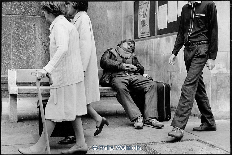 Homeless man sleeping on a bench, King's Cross, London 1990.