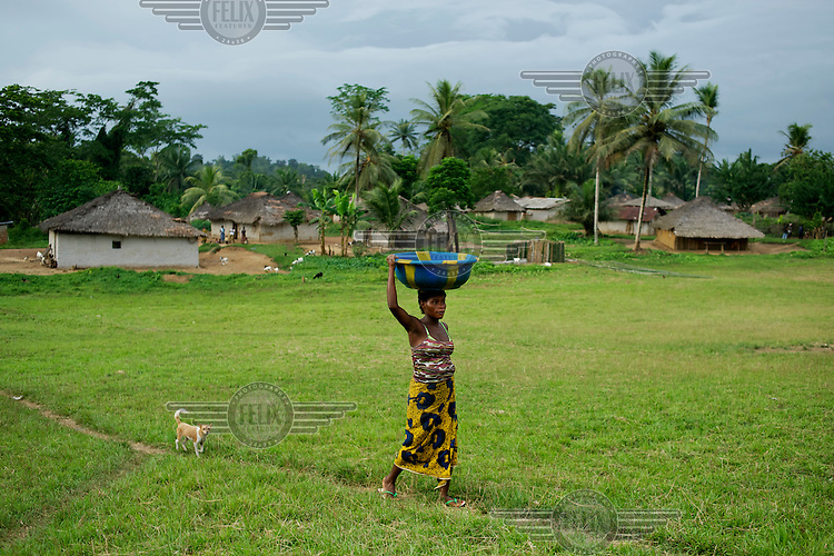 A woman carries a bowl above her head, followed by a small dog in the village of Jaytoken. /Felix Features