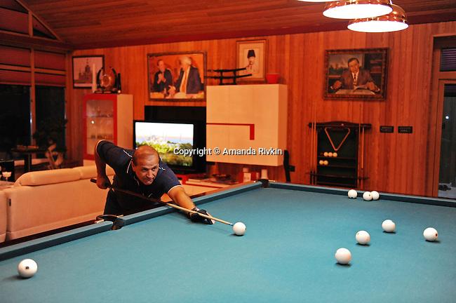 Ibrahim Ibrahimov plays billards after dinner in his home between Sangachal and Sahil, Azerbaijan on August 16, 2012.