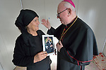 Bishop William Murphy of Rockville Centre, New York, blesses Rosa Majeed Nouri in a camp for displaced Iraqis in Dawodiya, Iraq, on April 10, 2016. She holds a photo of her son Fawaz, who was killed two months earlier while fighting against ISIS near Telskuf as a member of a Christian militia called the Nineveh Plain Protection Forces. <br /> <br /> Bishop Murphy came to northern Iraq with Cardinal Timothy Dolan, the archbishop of New York and chair of the Catholic Near East Welfare Association, and other church leaders to visit with Christians and others affected by ISIS. Murphy is also a member of CNEWA's beard.<br /> <br /> CNEWA is a papal agency providing humanitarian and pastoral support to the church and people in the region.