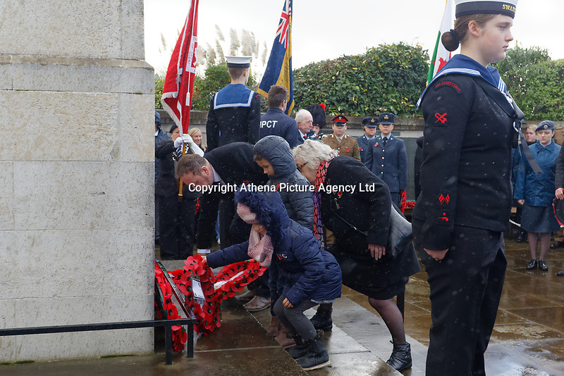 Pictured: Swansea Councillor Rob Stewart is joined by two children to lay wreaths. Sunday 11 November 2018<br /> Re: Commemoration for the 100 years since the end of the First World War on Remembrance Day at the Swansea Cenotaph in south Wales, UK.