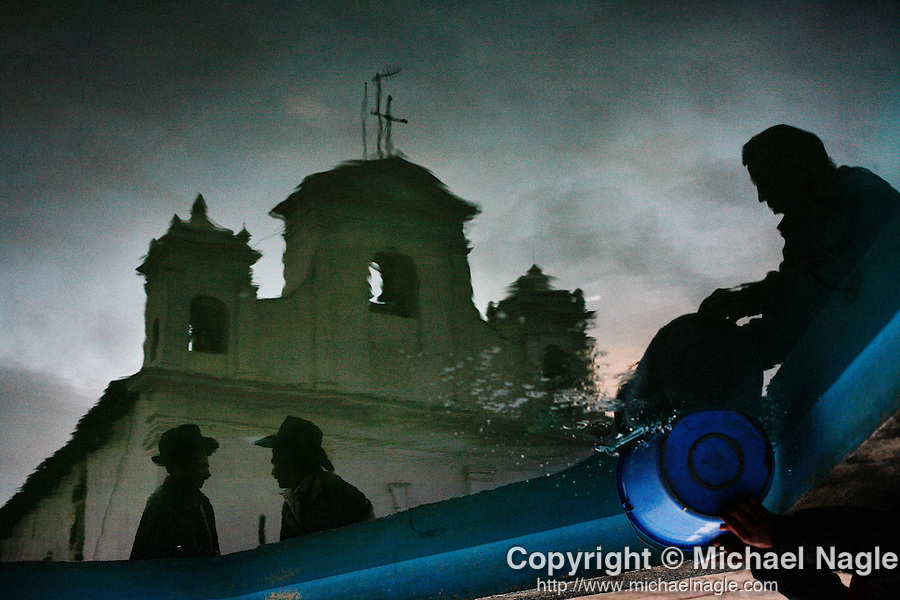 GUATEMALA  --  FEBRUARY 6, 2007: A man scoops a bucket into a pool of water as two men are reflected in front of the church in Nebaj on February 6, 2007 in Guatemala.  (PHOTOGRAPH BY MICHAEL NAGLE)