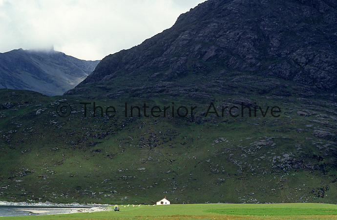 The fishing lodge is dwarfed by the looming mass of the Cuillin Mountains beyond Camasunary Bay