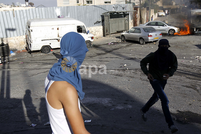 Palestinian youth throw stones towards Israeli security forces during clashes after Moataz Higazi was shot in east Jerusalem October 30, 2014. Israeli police shot and killed Higazi suspected of trying to kill a hard-line Jewish activist in Jerusalem, an incident that quickly sparked clashes between masked stone throwers and Israeli riot police, threatening to further enflame the already high tensions in the city. Photo by Muammar Awad