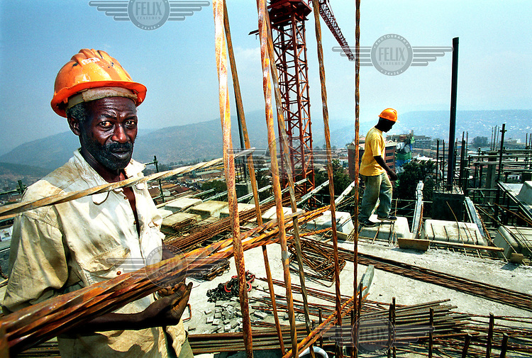 Construction worker on a building site. In recent years many new buildings have been added to the Kigali skyline. Some observers interpret this as confirmation that Rwanda has been enriched by the occupation and exploitation of Eastern Congo.