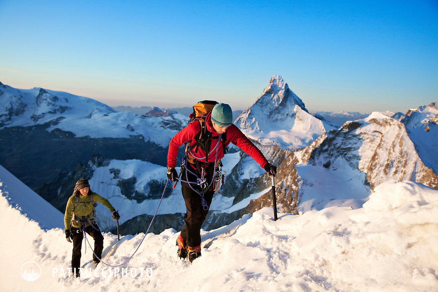 Two alpine climbers at sunrise in the Swiss Alps. The Matterhorn is behind them, high above Zermatt, Switzerland