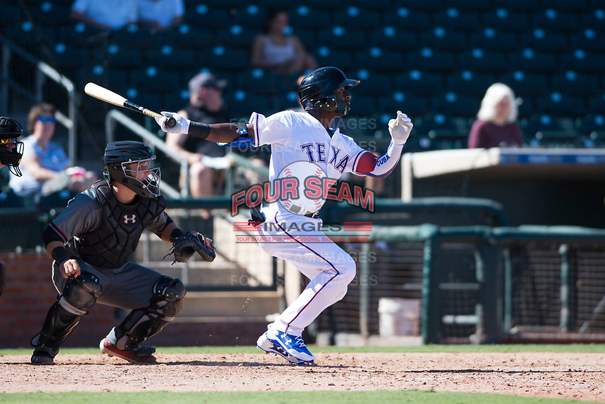 Surprise Saguaros outfielder Julio Pablo Martinez (40), of the Texas Rangers organization, follows through on his swing in front of catcher Daulton Varsho (8) during an Arizona Fall League game against the Salt River Rafters on October 9, 2018 at Surprise Stadium in Surprise, Arizona. Salt River defeated Surprise 10-8. (Zachary Lucy/Four Seam Images)