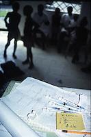 COLOMBIA  - Buenaventura -villaggio nella foresta colombiana  utilizzato per lo studio della malaria dall'OMS in quanto presenti le principali specie di zanzare anofele. Nell'immagine: adulti e bambini in un ambulatorio in attesa della vaccinazione. Su un tavolo siringhe e documenti per la vaccinazione.