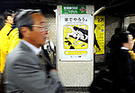 "Commuters walk past a poster requesting commuters refrain from lewd behavior on trains at an underground station in Tokyo, Japan. The Japanese are well known for their civility and politeness,  but a recent governmental campaign to clamp down on lewd behavior that may inconvenience others -- including talking on cell phones and applying makeup while commuting on a train -- was fueled by a decline in everyday etiquette and manners. The poster's headline reads ""Please do it at home."""