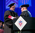 Brian Spittle, assistant vice president for the Center of Access and Attainment, receives a Via Sapientiae Award Sunday, June 11, 2017, from David Kalsbeek, senior vice president for enrollment management and marketing, during the DePaul University College of Science and Health and College of Liberal Arts and Social Sciences commencement ceremony at the Allstate Arena in Rosemont, IL. (DePaul University/Jamie Moncrief)