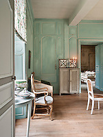A traditional reception room decorated in turquoise blue with white mouldings. Antique furniture is placed around the room.