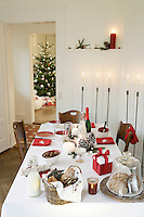 The table is laid for Christmas breakfast with red and white crockery and table linen