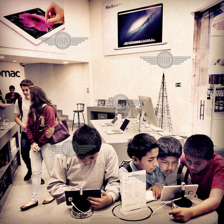 Children play on an iPad Mini in Paseo San Francisco, a new shopping centre in Cumbaya.