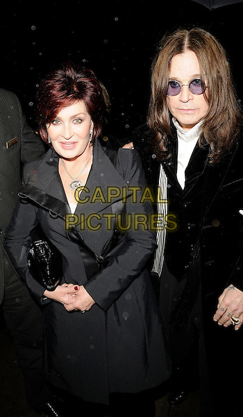 SHARON OSBOURNE & OZZY OSBOURNE  .The Classic Rock Roll Of Honour, Park Lane hotel, Piccadilly, London, England..November 3rd, 2008.half length black clutch bag grey gray coat jacket poppy tinted glasses sunglasses shades married husband wife.CAP/CAN.©Can Nguyen/Capital Pictures.