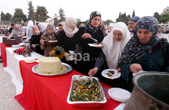 Palestinians serve food from the longest buffet table of natural and organic food, officially setting a new Guinness world record. on May 26, 2012 in Arab east jerusalem. The Palestinian banquet, prepared by Jerusalem locals, measured 202 metres. Photo by Mahfouz Abu Turk