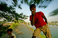 """""""It's no problem, watch me smoke and pose for you on a moving train,"""" said Helaluddin (18) who frequently travels like this on his off day from the plastic factory where he works."""