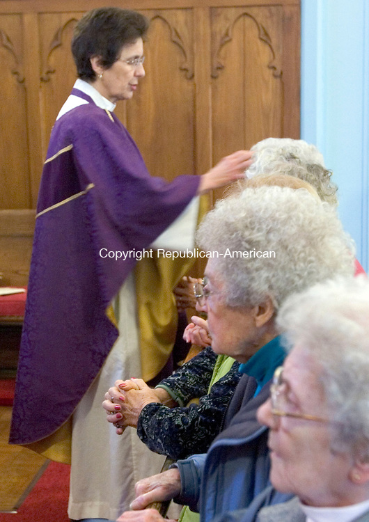 THOMASTON, CT. 09 March 2011-030911SV05-- Rev. Louise Kalemkerian administers ashes at St. Peter's Trinity Church in Thomaston Wednesday. Ash Wednesday is the beginning of the Lenten season and offered the imposition of ashes. The ashes are made from the burning of Palms from last year's Palm Sunday service. The Palms symbolize Jesus' triumphant entry into Jerusalem the week before His Crucifixion. Burning the Palms reminds us that as Christians we recognize that we are but dust and will return to dust.<br /> Steven Valenti Republican-American