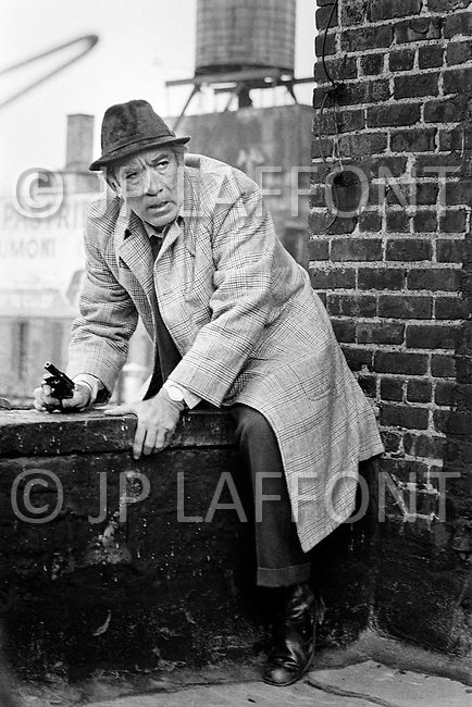 June 1972, Manhattan, New York City, NY, USA. Mexican born American Actor Anthony Quinn starring as detective Capt. Frank Mattelli on the roofs of Harlem in Across 110th Street, directed by Barry Shear.