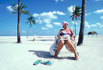 Portrait of old lady sitting on beach amongst palm trees, South Beach, Miami, Florida