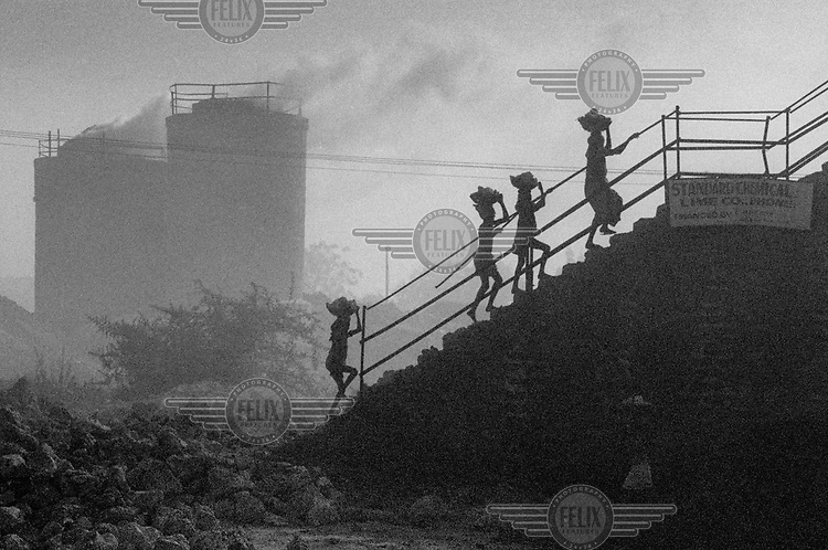 Women and children carry baskets of limestone up a set of steps at a lime kiln.